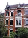 foto van Herenhuis met beneden- en bovenwoning en hek, gebouwd in overgangsarchitectuur met invloeden van de art nouveau in detaillering en materiaalgebruik