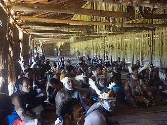 Asmat people - Asmat men inside their longhouse during a bisj pole completion ceremony, 2015.