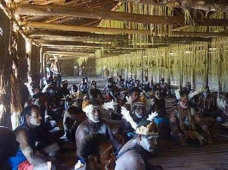 Asmat people - Asmat men inside their longhouse during a bisj pole completion ceremony, 2015.