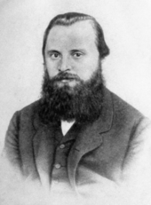 A man in his late 20s or early 30s with dark hair and a bushy beard, wearing a dark coat, dress shirt and tie