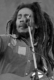 Black and white image of Bob Marley on stage singing into a mic