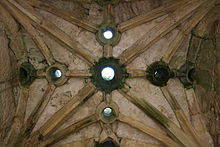 A vaulted stone ceiling. There are several circular holes in the ceiling.