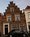 foto van Huis met grote trapgevel met natuurstenen banden, geblokte en geprofileerde natuurstenen waterlijst en dekplaten op de trappen