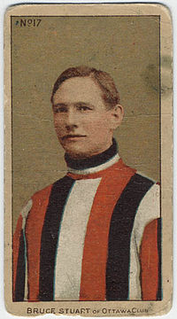 Brown-haired man in sweater of vertical red, black and white stripes