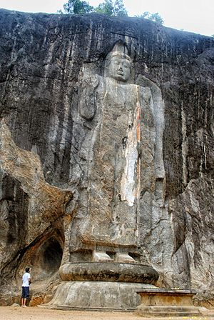 Buduruvagala - The gigantic standing Buddha – at 16m, it is the tallest on the island – in the centre still bears traces of its original stuccoed robe, and a long streak of orange suggests it was once brightly painted