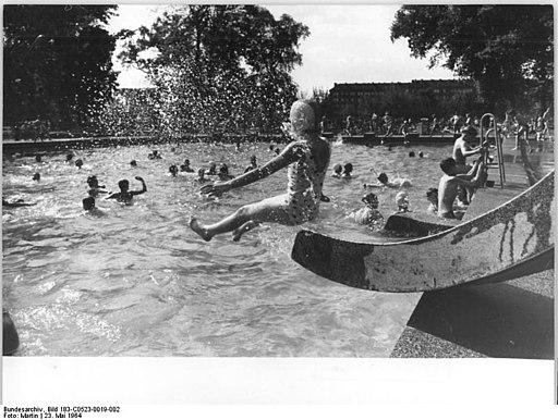 Junges Mädchen im Moment des Abflugs von der Rutsche ins Becken des Freibads Friesenstadion.