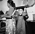 COLLECTIE TROPENMUSEUM Portret van een meisje dat een blad op het hoofd draagt met gebakken banaan voor de verkoop TMnr 20000272.jpg