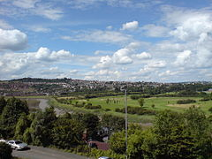 A photograph taken from a house window on Caerleon Road in St Julians. The view crosses the river Usk and in the distance is the Caerleon Golf Club, and behind it, the settlement of Caerleon, on the hill with rows of houses visible. At the far right are the visible buildings of Caerleon Comprehensive School and its sports facilities.