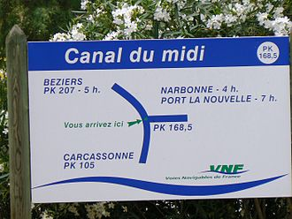 "Kilometric point - ""You are here"" sign on the Canal du Midi just before the turn onto La Nouvelle branch. Note that locations on this French canal are marked in PK values."