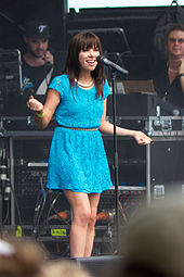 A Caucasian female with shoulder-length, wavy brown hair and wearing a powder blue dress sings and pearls into a microphone on stage, extending both arms in an emphatic gesture.