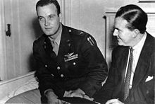 A monochrome photograph of two men, one about 30 years old wearing a military pilot's uniform of the rank colonel, seated, leaning forward to the left, looking left, and the other in his mid-40s wearing a suit jacket, white shirt and tie, with dark hair oiled, parted and combed