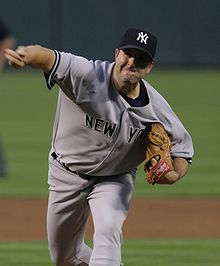 "A man in a gray baseball uniform with ""New York"" across the chest in navy-blue letters and wearing a navy blue baseball cap with an interlocking white ""NY"" on the front"