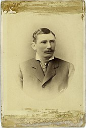 A sepia-toned image of a mustachioed man in a dark Victorian suit