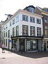 foto van Hoekpand Oude Delft. Pand ter diepte van zes assen, parterre en twee verdiepingen, schilddak. Eenvoudige voorgevel met lage bovenverdieping en kroonlijst