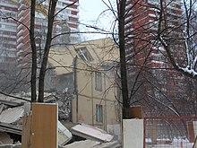 Restene av en lav bygning er sett mellom to høyhus