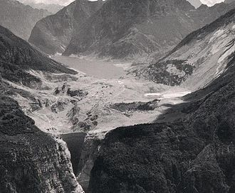 Vajont Dam - Aerial view of the 'Valley-Vajont' area shortly after the disaster showing the lake filled with mud and debris from the landslide. The dam is in the foreground at left.