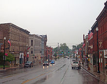 A wide, wet street with tall commercial buildings on either side. Two approaching vehicles have their headlights on, and a traffic light behind them is green. In the rear of the image the street narrows to go over a small bridge.