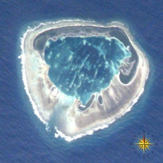 "A satellite photograph of an atoll consisting of four islets with an interior lagoon. The largest island has a ""C"" shape and is dominated by vegetation. The other three are smaller and have sparse vegetation. The islets are surrounded by dead coral and the ocean. In the lower right corner of the photo, a compass indicates the orientation of the island."