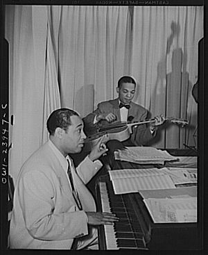 Duke Ellington directing his band from the pia...