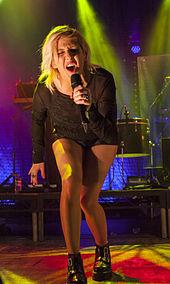 Una mujer cantando en un micrófono, el uso de ropa de color negro.  En el fondo, tambores y platos se pueden ver.