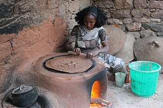 Injera - Woman checking the backing of an injera in her house. Gheralta, Ethiopia