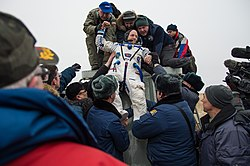 Scott Kelly being carried from the Soyuz TMA-18M spacecraft
