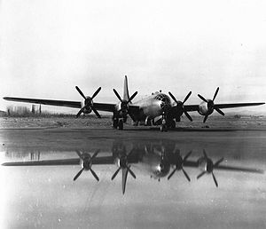 Black and white photo of a military aircraft powered by four propeller engines parked in an open area