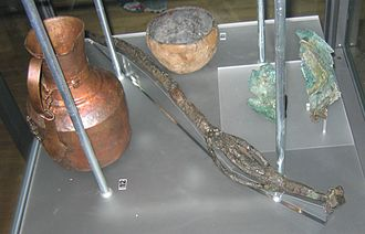 Völva - Finds from a vǫlva's grave in Köpingsvik, Öland. There is an 82 cm long wand of iron with bronze details and a unique model of a house on the top. There is also a pitcher from Persia or Central Asia, and a West European bronze bowl. Dressed in a bear pelt, she had received a ship burial with both human and animal sacrifice. The finds are on display in the Swedish History Museum in Stockholm.