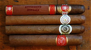 Four cigars of different brands (from top: H.