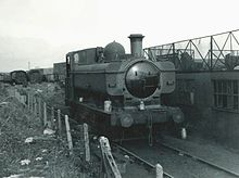 A pannier tank locomotive stands alone in a scrapyard next to a semi-derelict building. In the background are other locomotives waiting to be scrapped. To the left is a fence of concrete posts with wire.