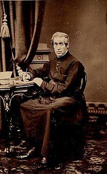 A man is pictured sitting down, facing the camera. His right hand is holding a pen to paper which sits on a table to the man's right, and his left hand rests on that table. The man is dressed in the clothes of a Christian religious leader.
