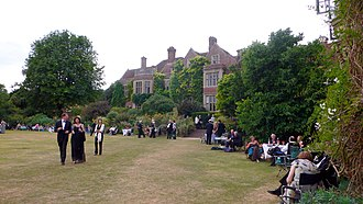 extensive gardens with English country house in the background