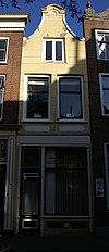 Huis met gepleisterd klokgeveltje met segmentvormige afdekking en hoekvoluten