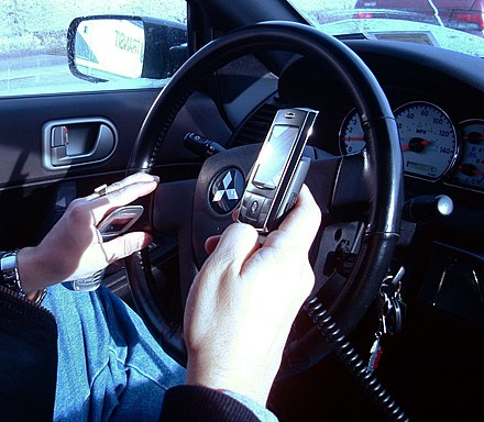 A New York City driver holding two phones Hand held phones.JPG