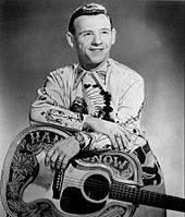 A man wearing an elaborately patterned shirt, leaning on a guitar