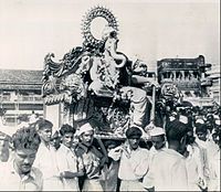 Statue of Ganesha on a throne being carried on many shoulders