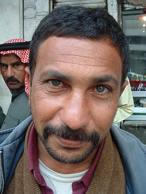 An Iraqi man pauses for a photo on a Baghdad street near the main market, with an interesting looking man passing by in the background.