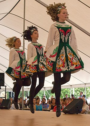 Irish dance - Irish dancers in modern Irish dancing costumes, wearing makeup and ringleted wigs for performance display