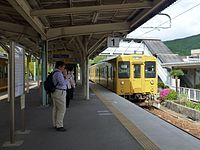 JNR 105 Setouchi yellow livery Kure Line train at Takeura Station.jpg