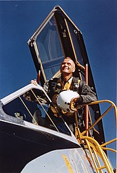 Photo of John Glenn leaning out of a cockpit looking into the distance