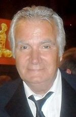 A man with grey hair, wearing a black suit, including a black tie and a white shirt.