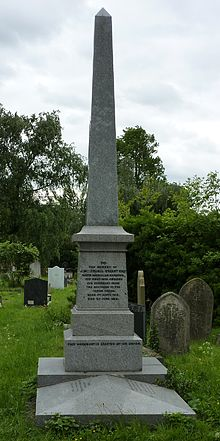 A polished, grey, obelisk-like funerary monument surmounting a grave