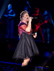 An image of Clarkson, wearing a sequined fuchsia and black dress against a dark background.