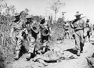 Kenneth Eather - Australian troops file past a dead Japanese soldier on their way in to Lae.