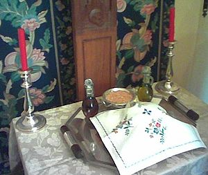 Lity (Orthodox Vespers) - Artoklasia table in the Russian tradition. The five loaves in the front are covered with an embroidered cloth. At the back center is a dish of wheat, and at the sides are a vessel of olive oil and a cruet of wine.