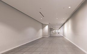 Long corridor with someone sitting on the floor in the distance at Marina Bay MRT Station Singapore.jpg