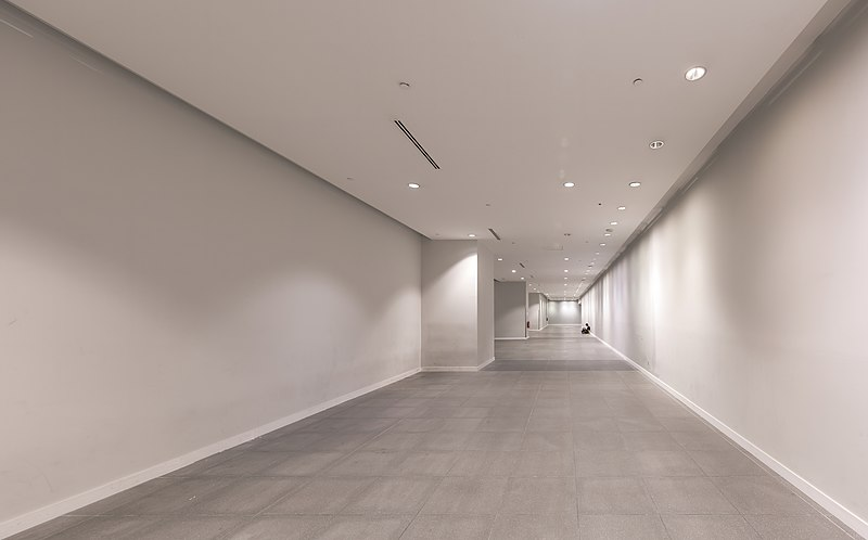 File:Long corridor with someone sitting on the floor in the distance at Marina Bay MRT Station Singapore.jpg