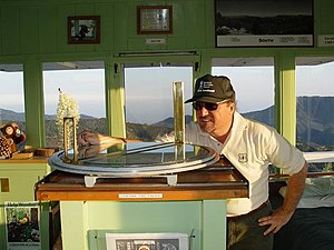 "Fire lookout tower - A fire lookout uses an Osborne Fire Finder to obtain the azimuth and distance to a suspected fire. From these measurements he will call in a ""Smoke Report""."