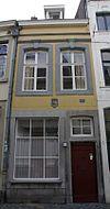 foto van Huis met lijstgevel, van mergel met vensters in uitspringende segmentboogomlijstingen onder een bij de sluitstenen omgekorniste profiellijst.
