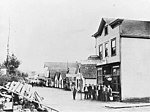Main Street showing businesses and group of men standing outside the Post Office, Tenakee, Alaska, probably 1901 (AL+CA 2315).jpg
